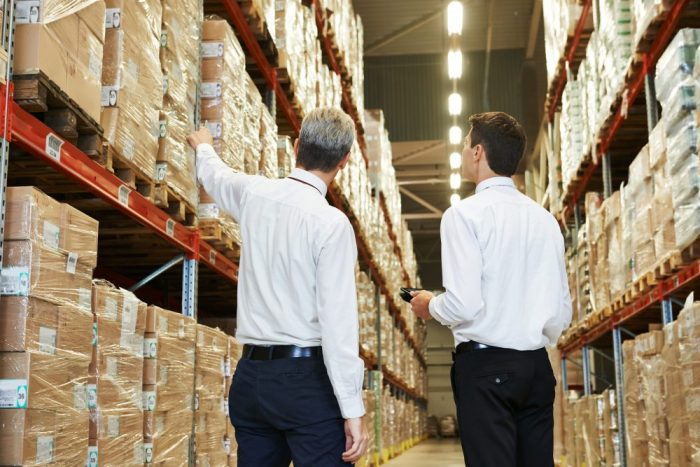 Two men in business attire viewing warehouse inventory